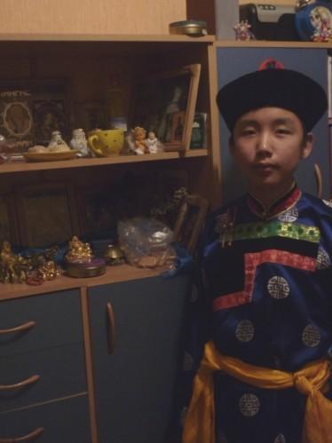 Le grand-frere de Liana dans son costume Bouriate, aupres des Bouddhas de la maison